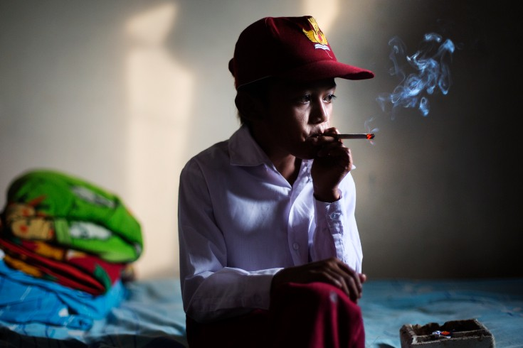 A primary school student smokes in his room, in his school uniform. This habit is common among kids in Indonesia. In fact, the average earliest smoking age is 7 years old. (Source: Arrahmah.com)